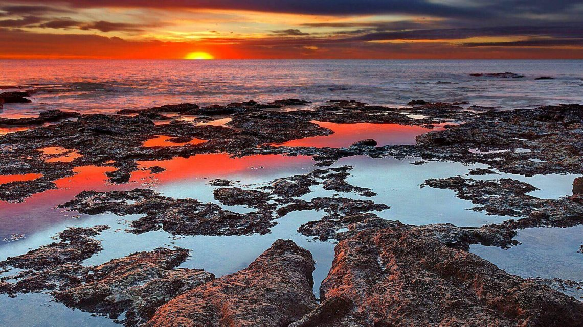 Tidal pools reflect the sunrise colors during the autumn equinox